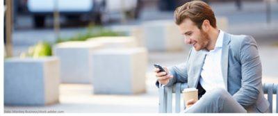 Mann auf Parkbank mit Kaffee und Handy