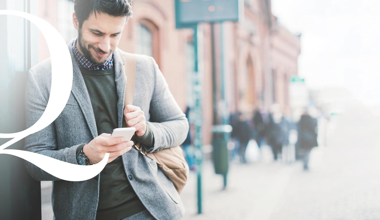 Mann wartet an Haltestelle mit Handy