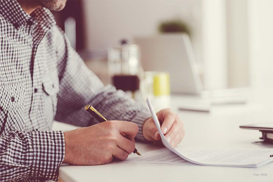 Person unterzeichnet Unterlagen